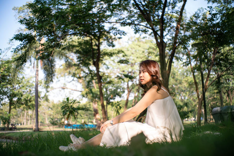 Side view of thoughtful woman sitting on land in park