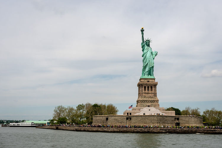 New York, USA - June 7, 2019: Ferry Boat approaching the Statue of Liberty, Liberty Island - Image Liberty Statue Ferry Manhattan USA Tourism City Freedom Boat River Travel Landmark America Sky Island Water NYC Downtown York Skyscraper Hudson Skyline Cityscape New United Urban American Building Architecture Transportation Blue Monument State Tourist Staten Torch View Metropolitan History Icon Symbol Attraction Ship Metropolis Modern Harbor Day Cruise New York Scenic Sculpture Human Representation Travel Destinations Representation Female Likeness Art And Craft Cloud - Sky Nature Waterfront Built Structure No People Outdoors Independence Turquoise Colored