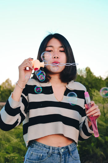 Portrait of beautiful young woman holding bubbles