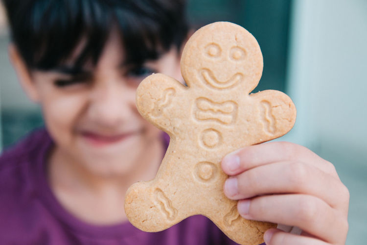 Close-up portrait of boy holding cookie man