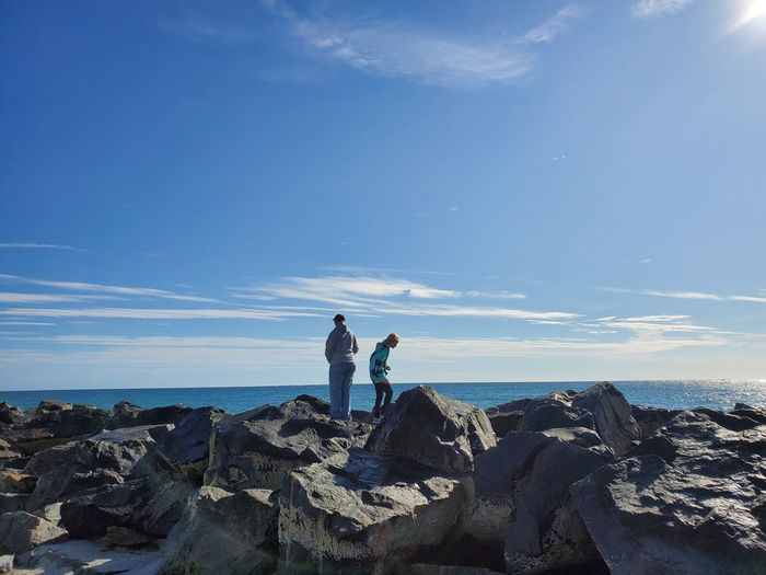 People standing on rock by sea against blue sky