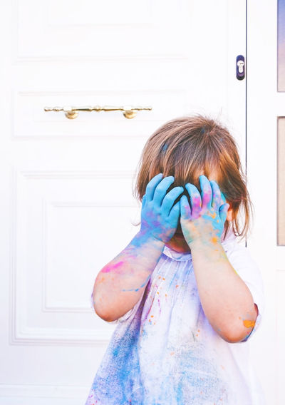 One Person Real People Child Front View Door Unrecognizable Person Obscured Face Indoors  Childhood Entrance Women Waist Up Standing Females Portrait Leisure Activity Hiding Hairstyle Lifestyles Innocence Human Face Holi Hands Covering Eyes
