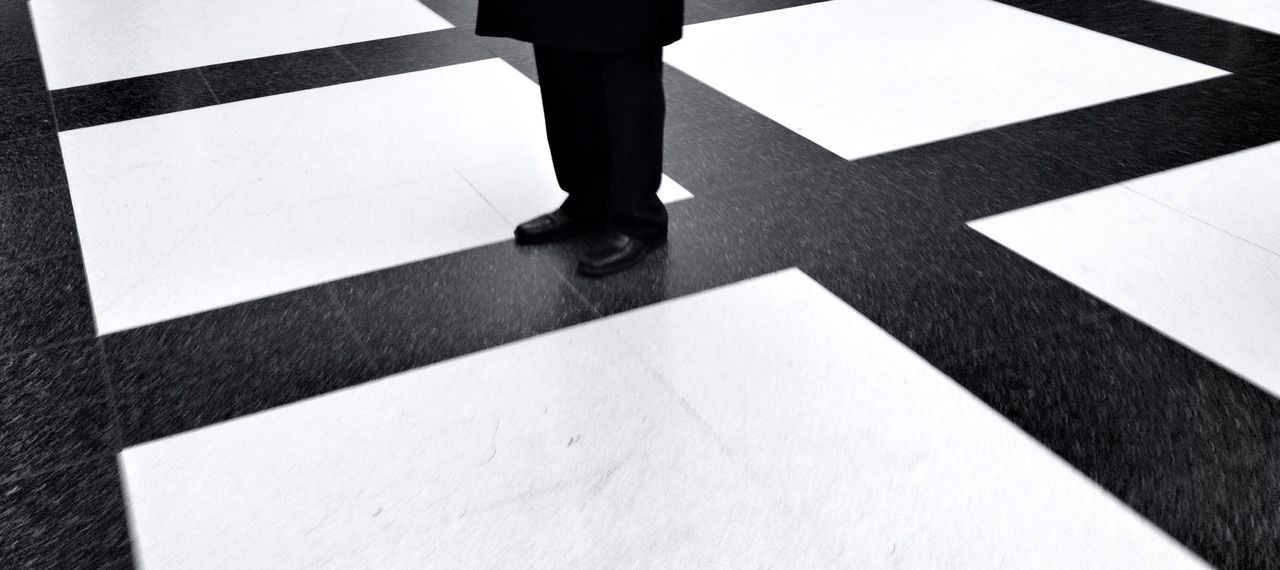 Low section of businessman standing on tiled floor