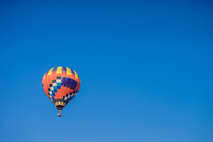 Adventure Air Vehicle Balloon Ballooning Festival Blue Clear Sky Copy Space Day Extreme Sports Flying Hot Air Balloon Low Angle View Mid-air Mode Of Transportation Multi Colored Nature No People Outdoors Parachute Sky Transportation Travel