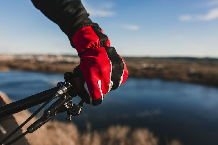 Cropped hand of person riding bicycle by river against sky
