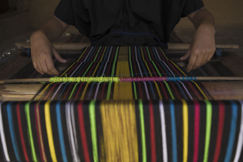 Midsection Of Person Weaving Colorful Loom