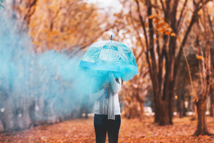 Woman with umbrella and distress flare standing at park during autumn