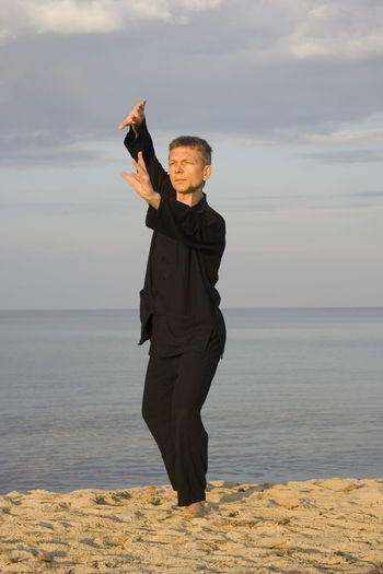 Full length of man performing tai chi while standing against sky