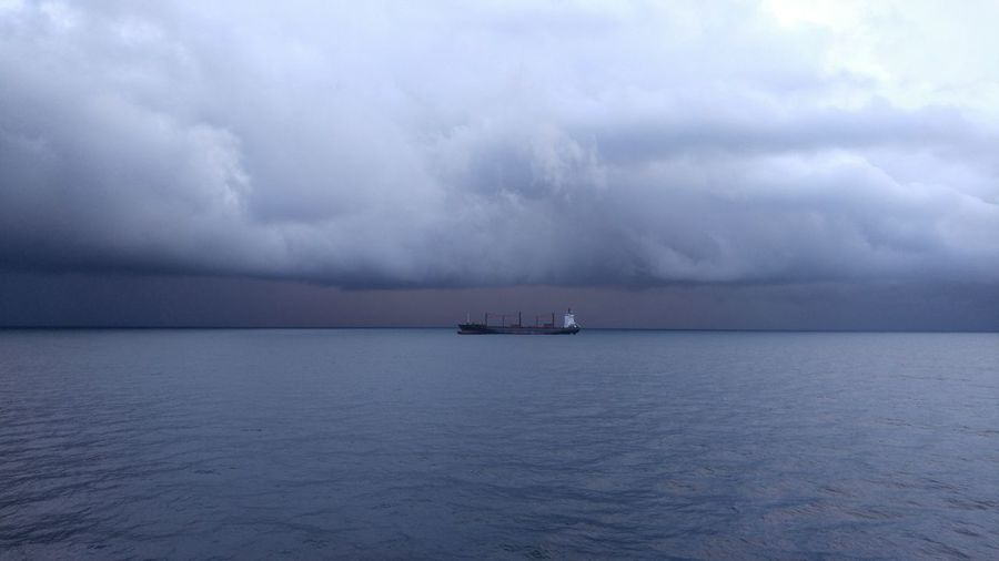 Scenic view of ship in sea against storm clouds