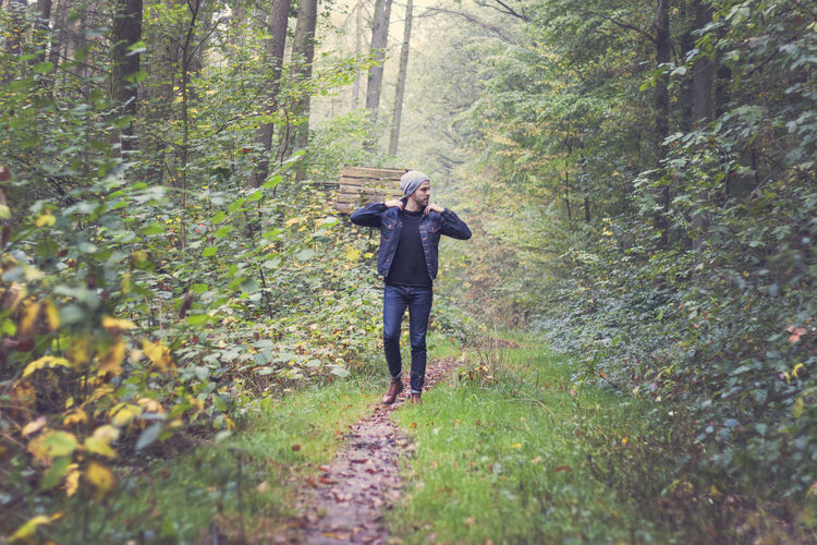 Full length of man walking on trail in forest