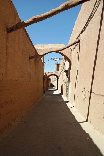 Narrow alley amidst buildings against sky