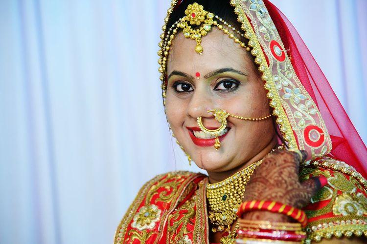 Close-up portrait of bride wearing sari against curtain