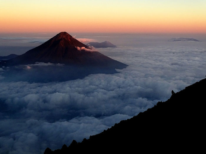 Aerial view of mountain covered with clouds during sunset