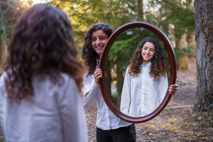 Smiling woman holding mirror in front of sister at forest