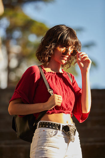 Midsection of woman holding red while standing outdoors