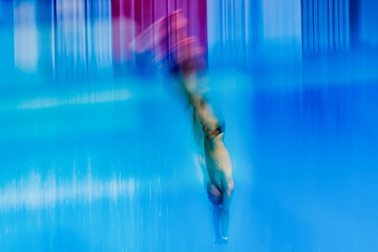 Blurred motion of shirtless man diving into swimming pool