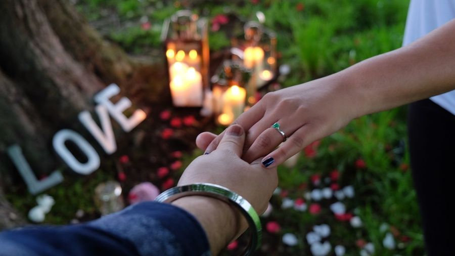 Cropped image of couple holding hands by candles on field