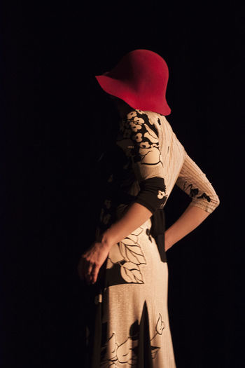Girl in the dark Studio Shot Standing Black Background Three Quarter Length Creativity Women Clothing Arts Culture And Entertainment Hat Red Hat Back Shot  Dark Young Women Actress On Stage Pavia Indoors  Hidden Faces Floral Dress