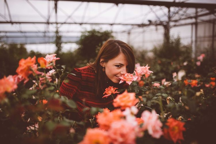 Portrait of woman with red flowers in greenhouse