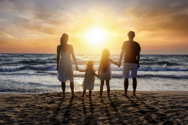 A family enjoys the summer sunset on their summer vacations on the beach Beach Sunset Sea Water Sky Horizon Over Water Group Of People Real People Standing Lifestyles Sand Cloud - Sky Leisure Activity Outdoors Horizon Family Vacations Holiday Summer Togetherness Parents Holding Hands Happy Freedom Love