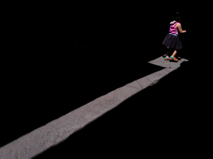 High angle view of woman standing against black background