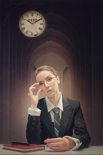 Young businesswoman sitting on table