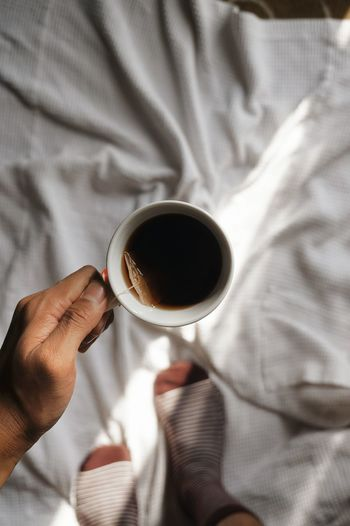 Cropped Image Of Woman Holding Coffee Cup On Bed