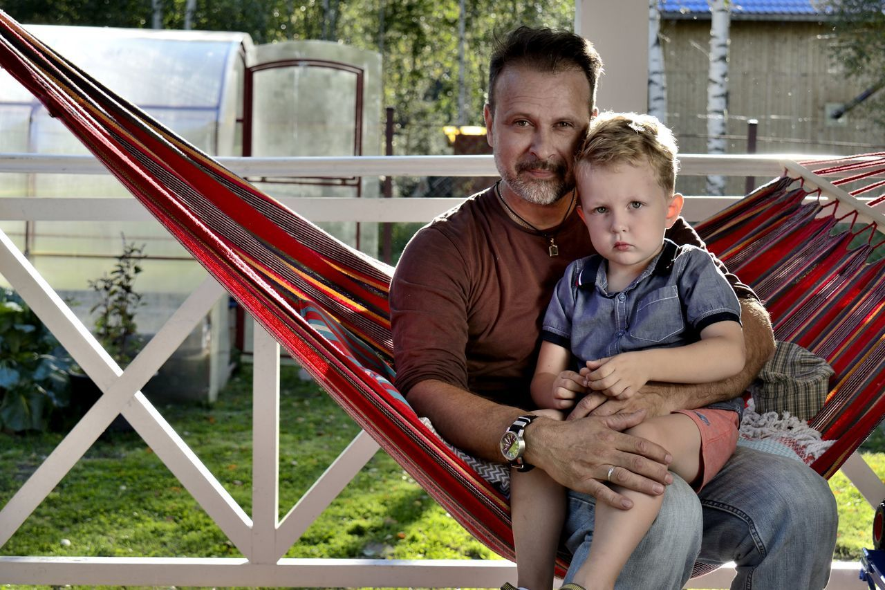 Portrait Of Father Sitting With Son On Hammock