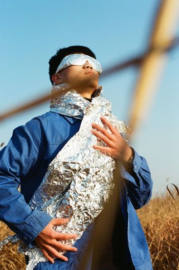 Low angle view of man with aluminum foil standing on field against sky