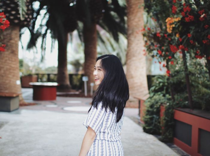 Smiling young woman standing at park