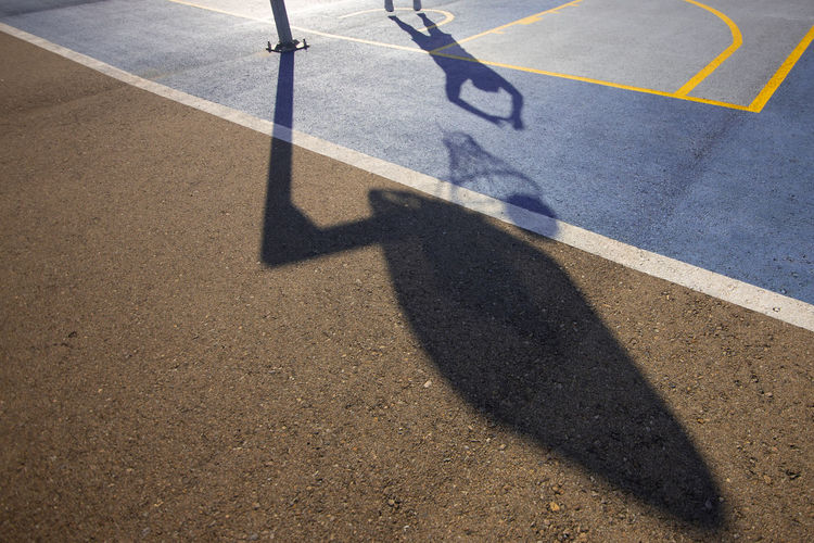 High angle view of shadow of man playing basketball at court