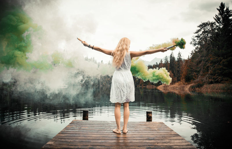 Rear view of woman holding distress flare standing by lake against sky