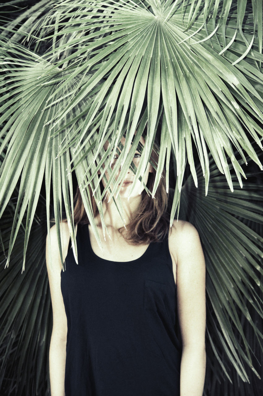 Portrait Of Young Woman Standing By Palm Tree