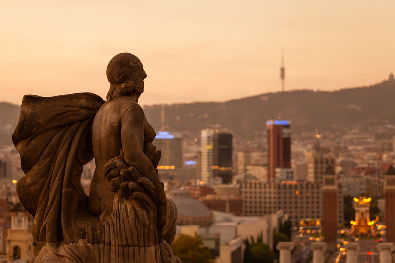 High Angle view of Barcelona at sunset with statue in foreground Architecture Statue Human Representation Sculpture Building Exterior City Sky Sunset Cityscape Travel Destinations Building No People Skyscraper SPAIN Barcelona Viewpoint Summer