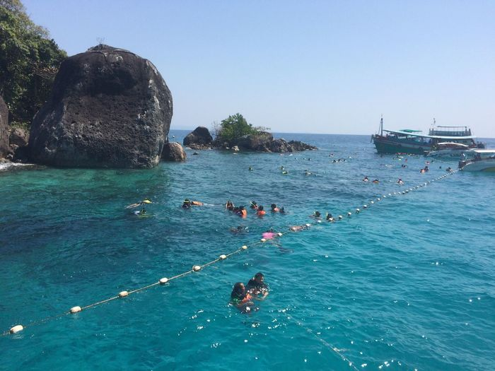 People swimming in sea against clear sky