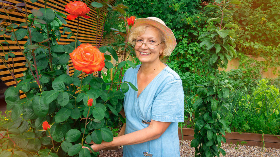Portrait of smiling senior woman standing by plants
