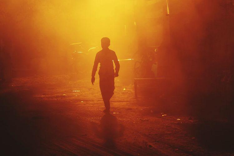 Silhouette man walking on road at night