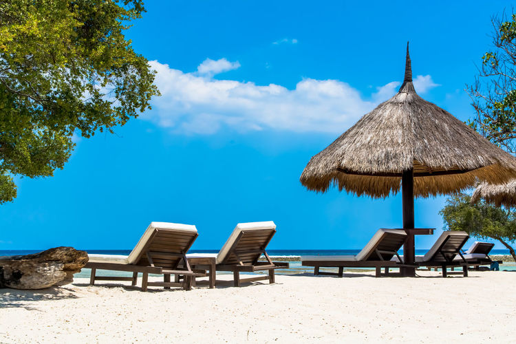 Parasol By Lounge Chairs On Sand At Beach Against Sky