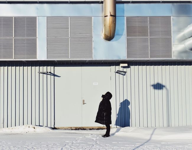 Full length of woman standing in front of building during winter