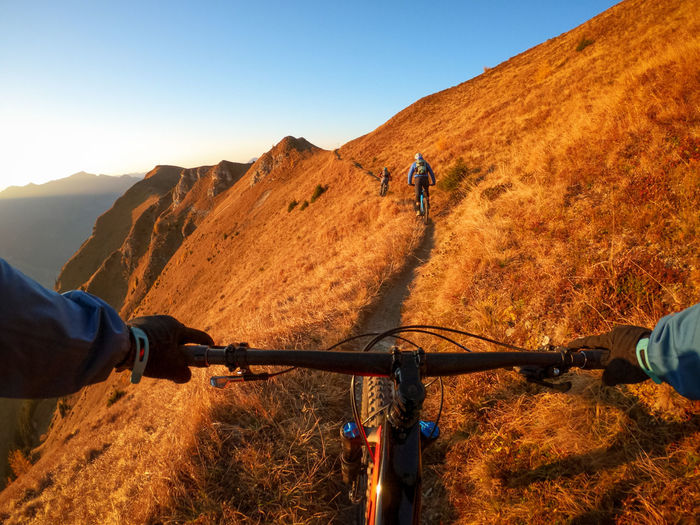 Cropped image of man riding bicycle on mountain