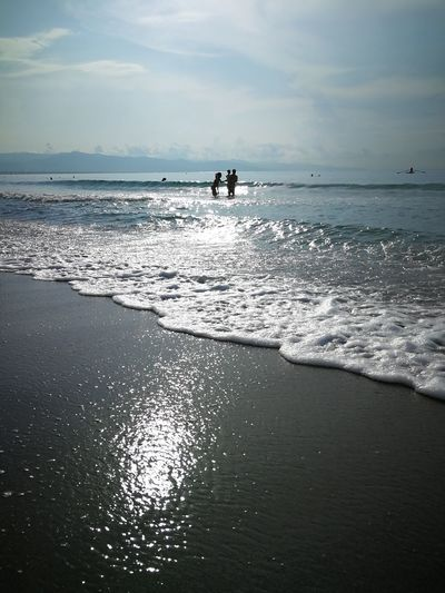 Distant view of people in sea against sky