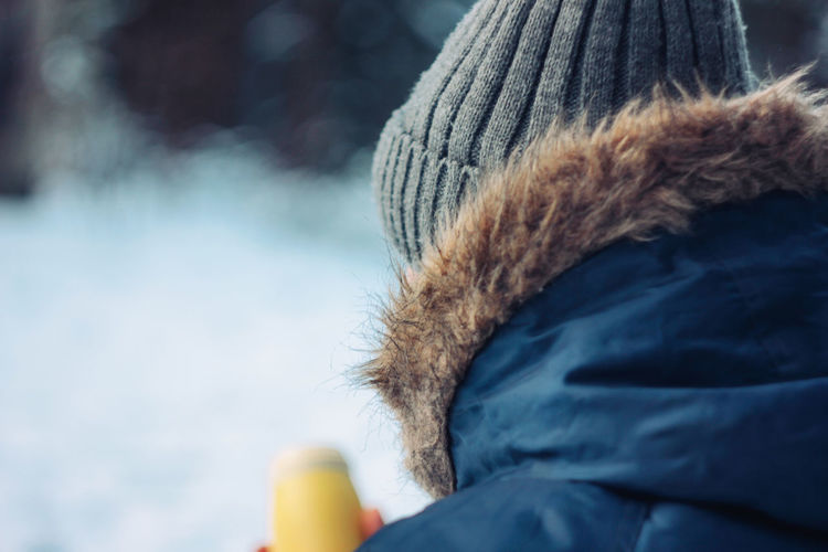 Close-up of person wearing hat during winter