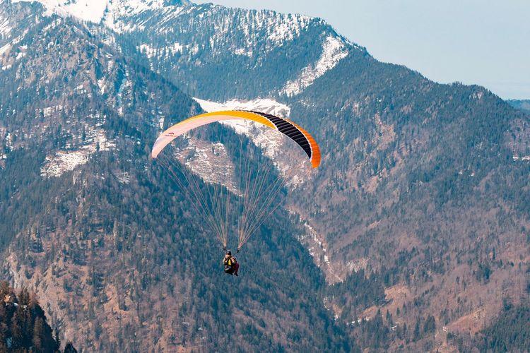 Person paragliding against mountain range