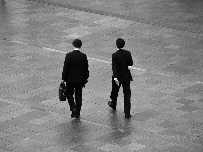 Rear View Of Businessmen Walking On Street