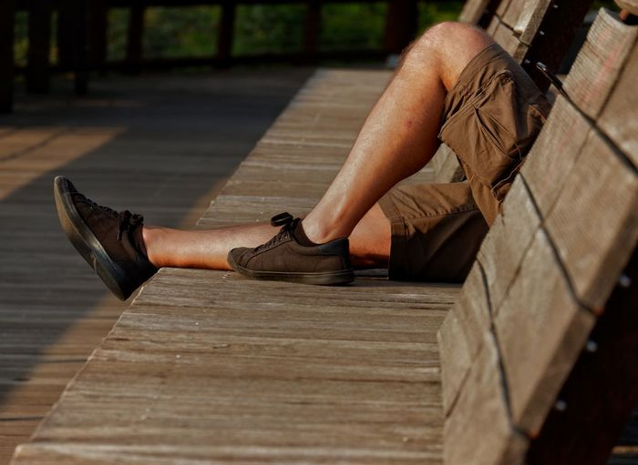 The legs with a pair of black shoes at the feet of a european man lying on wooden bench