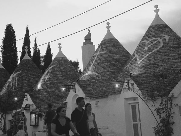 Alberobello Alberobello - Puglia Alberobello City Alberobellocity Alberobelloexperience Alberobellophotocontest Architecture Building Exterior Built Structure Day History Lifestyles Men Outdoors Place Of Worship Real People Religion Sky Spirituality Tree Women The Street Photographer - 2017 EyeEm Awards
