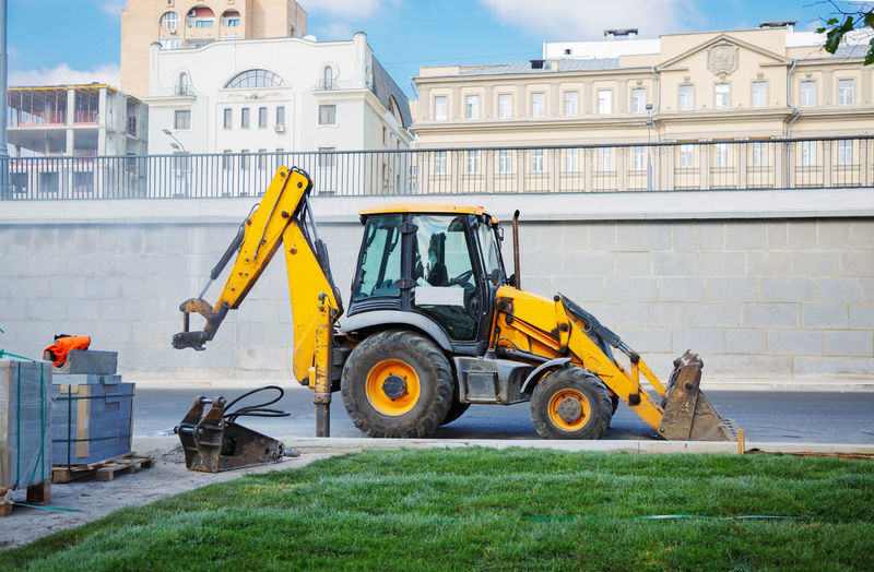 View of bulldozer on road against building