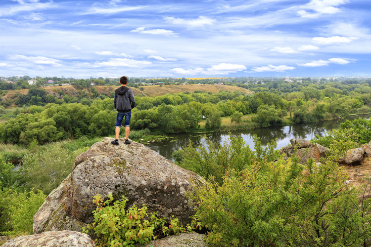 Rear view of boy standing on rock against sky