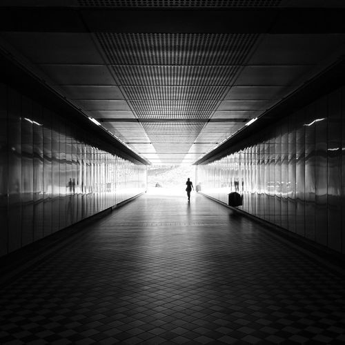 Distance View Of Woman Walking In Tunnel