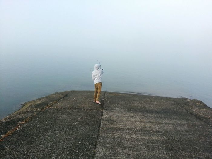 Rear view of person fishing at jetty during foggy weather